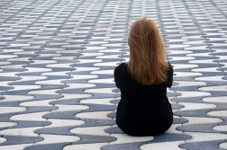 Girl sitting on colorful flagstones. She turned her back which causes a feeling of loneliness.