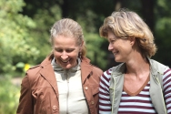 Closeup portrait of two attractive middle-aged female friends chatting in the park in a healthy lifestyle concept