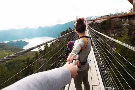 woman with yellow backpack standing on hanging bridge with trees